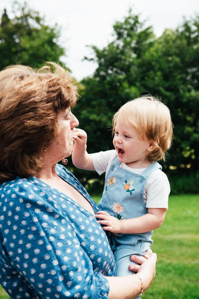 Virginia Water Family Photography, Grandmother and grandchild laugh towards the camera