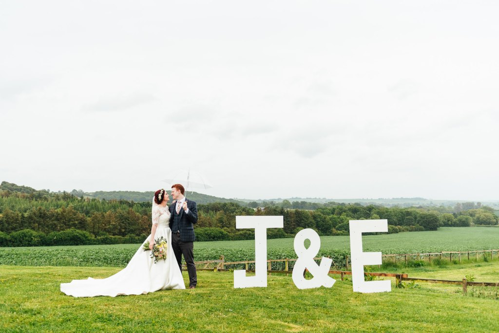 Creative couples portrait with home made initial signs