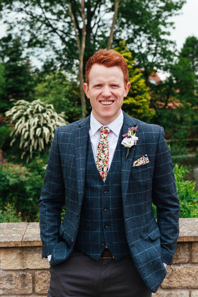 Handsome groom in a navy blue tartan suit