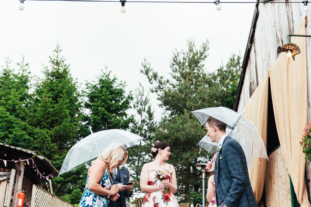 Guests hide under umbrellas for rainy Yorkshire wedding