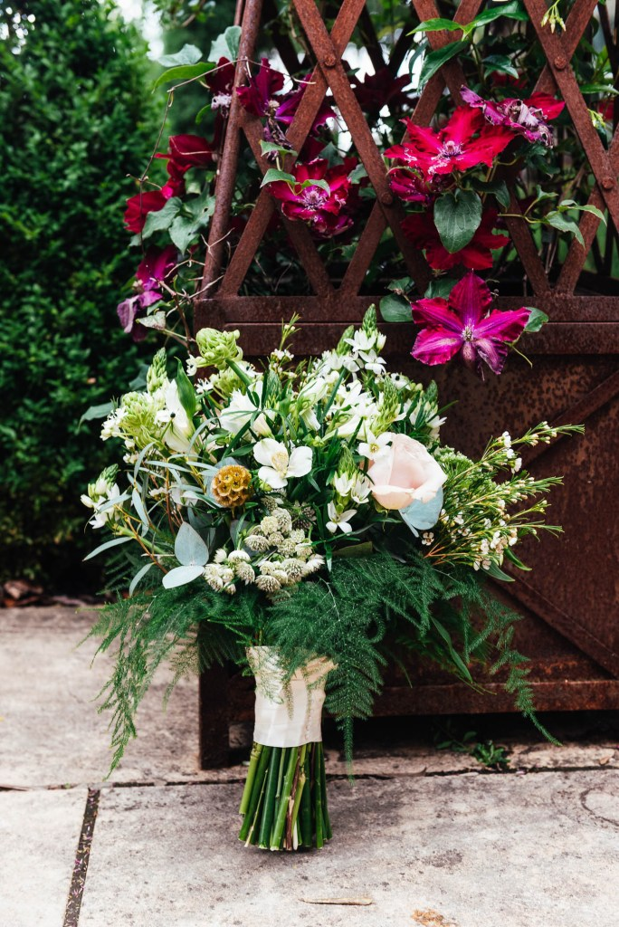 Wedding bouquet arranged with white flowers and green foliage