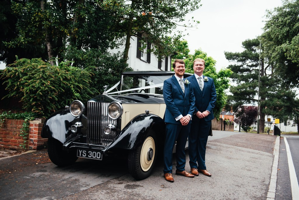 Groom and best man stand with Vintage wedding car