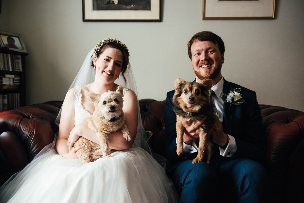 Bride and groom spend a moment with their dogs on their wedding day