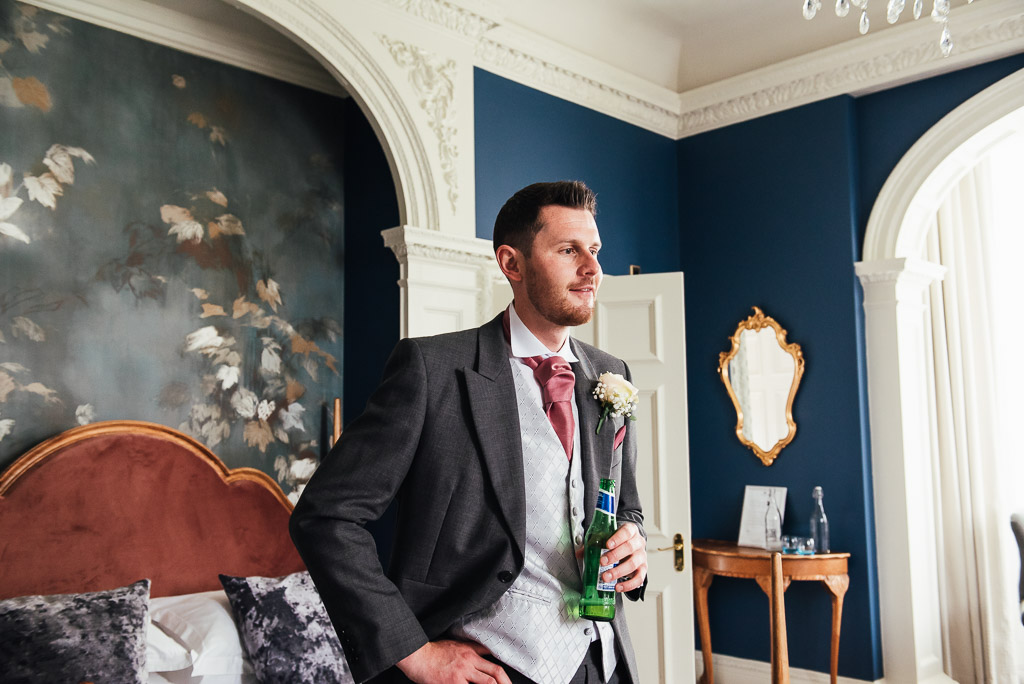 Groom shares a beer whilst getting ready