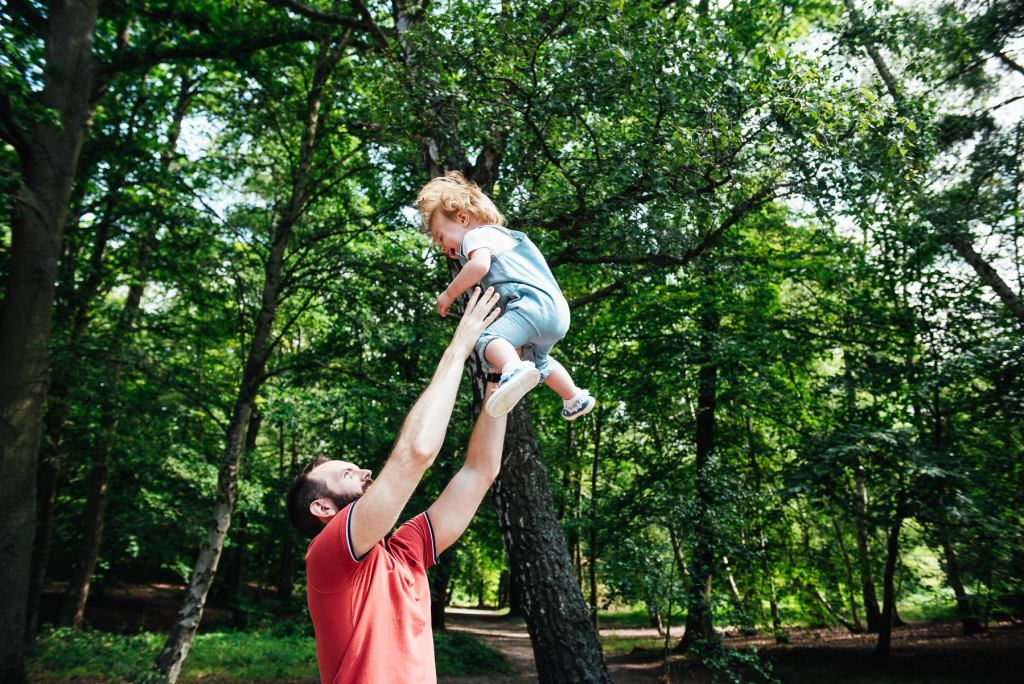 Father playfully throws his daughter up in the air on an outdoor family photoshoot