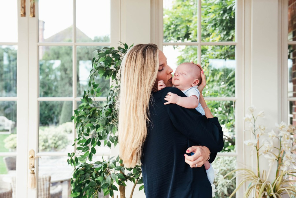 Mother lovingly holds her child in light and airy conservatory