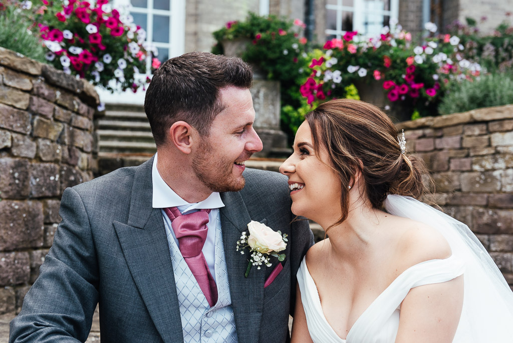 Couple lovingly look into each others eyes for a natural wedding portrait