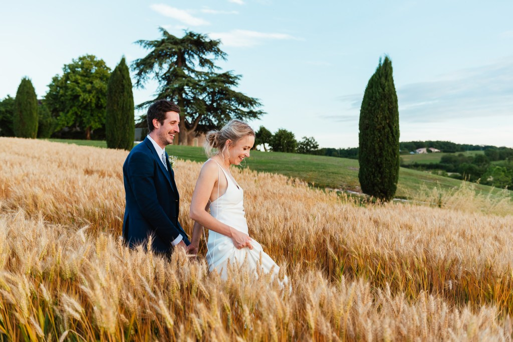 Couple walk together in the wheat fields for destination wedding photography France