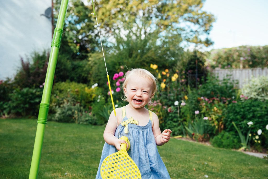 Smiley and happy little girl plays outside on Surrey family shoot