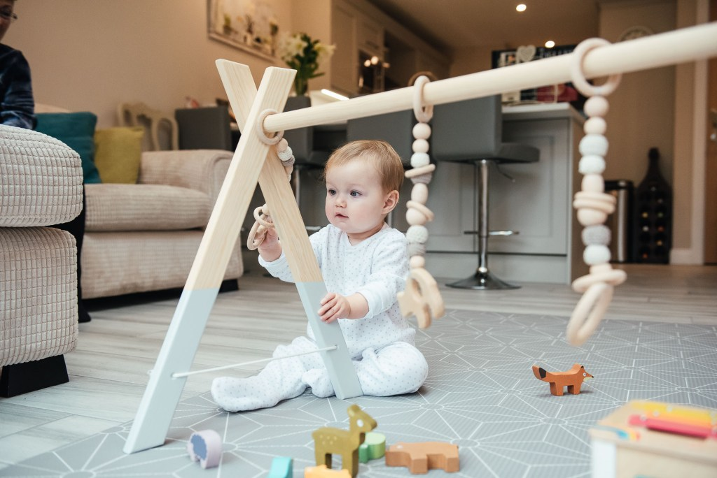 Gorgeous baby playing with wooden toys in Surrey family photo shoot