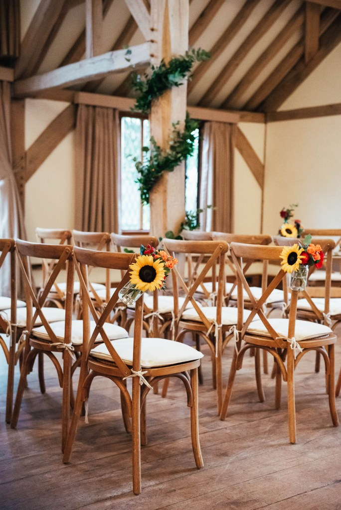 Cain Manor wedding venue with wooden chairs and autumnal florals