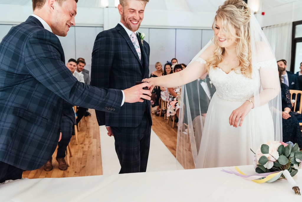 Best man hands the rings to the wedding couple