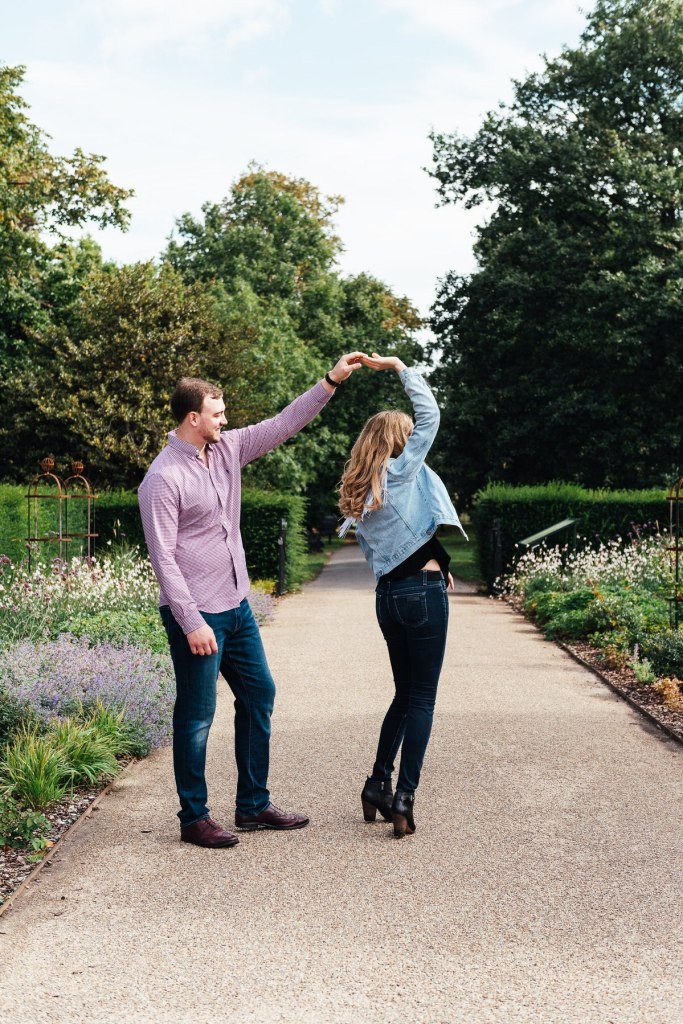 Engaged couple dance together in a London garden