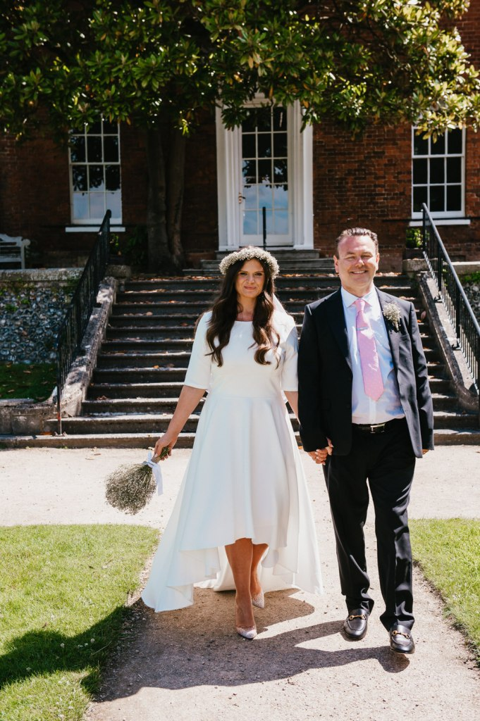 Newly married couple walk in the grounds of registry office together