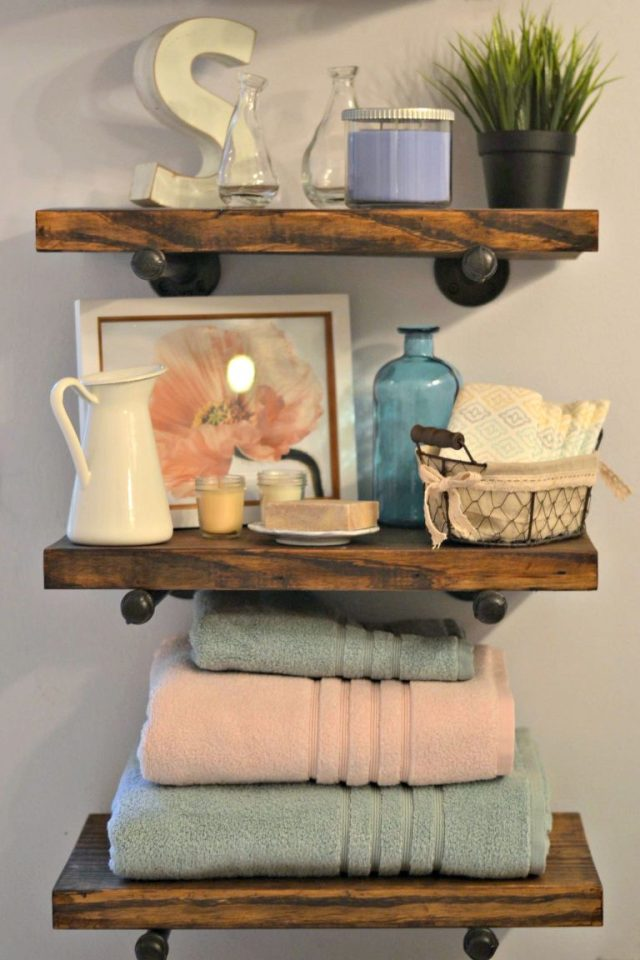 This bathroom renovation takes a drab room to a rustic-modern haven, and this post shares how we did it without breaking the bank. Create floating shelves out of wood, with pipes to hold them up.