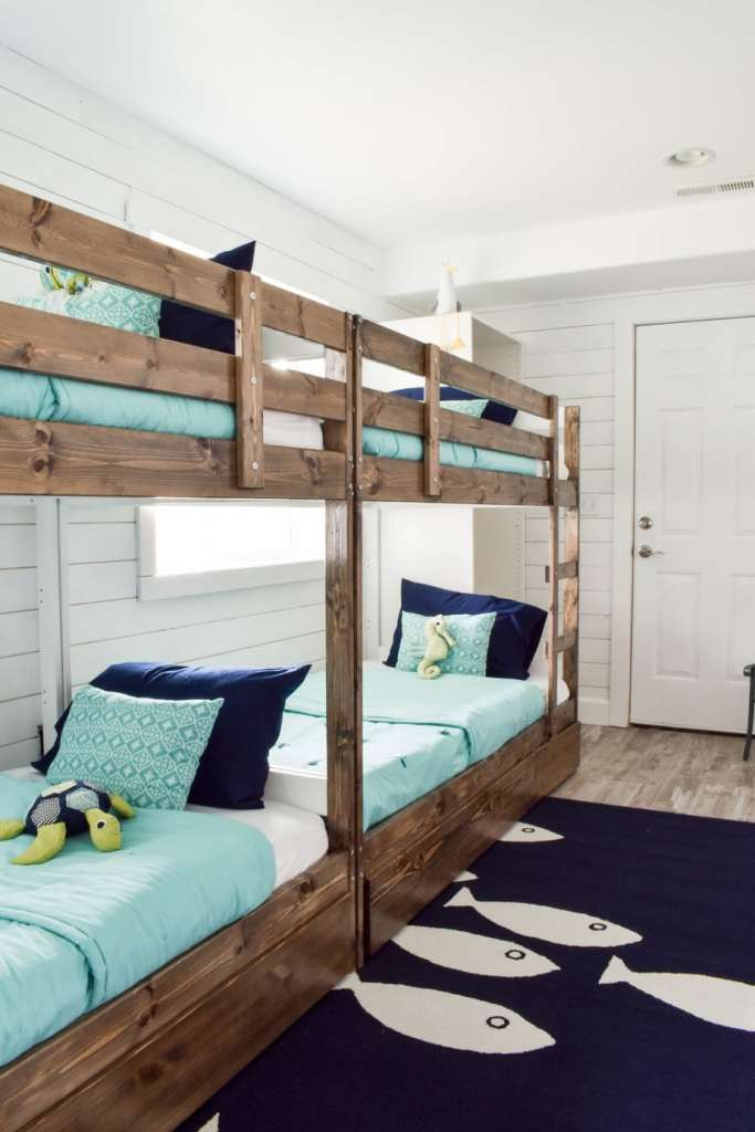 This fun ocean-themed beach house bunk room is the perfect vacation sleepover and play room for the kids. The Ikea beds have ladders and built-in storage.