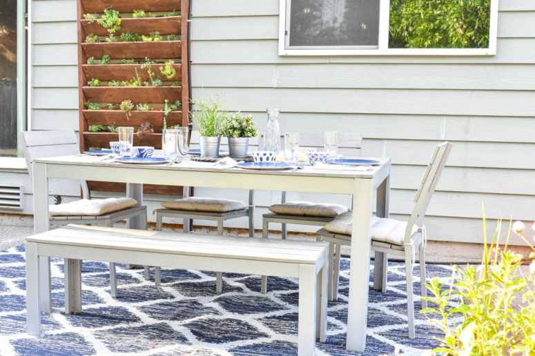 This simple and budget-friendly dining patio makeover transforms a small ugly concrete slab patio into a beautiful outdoor dining room. There's a vertical garden, string lights, an outdoor rug, and more!