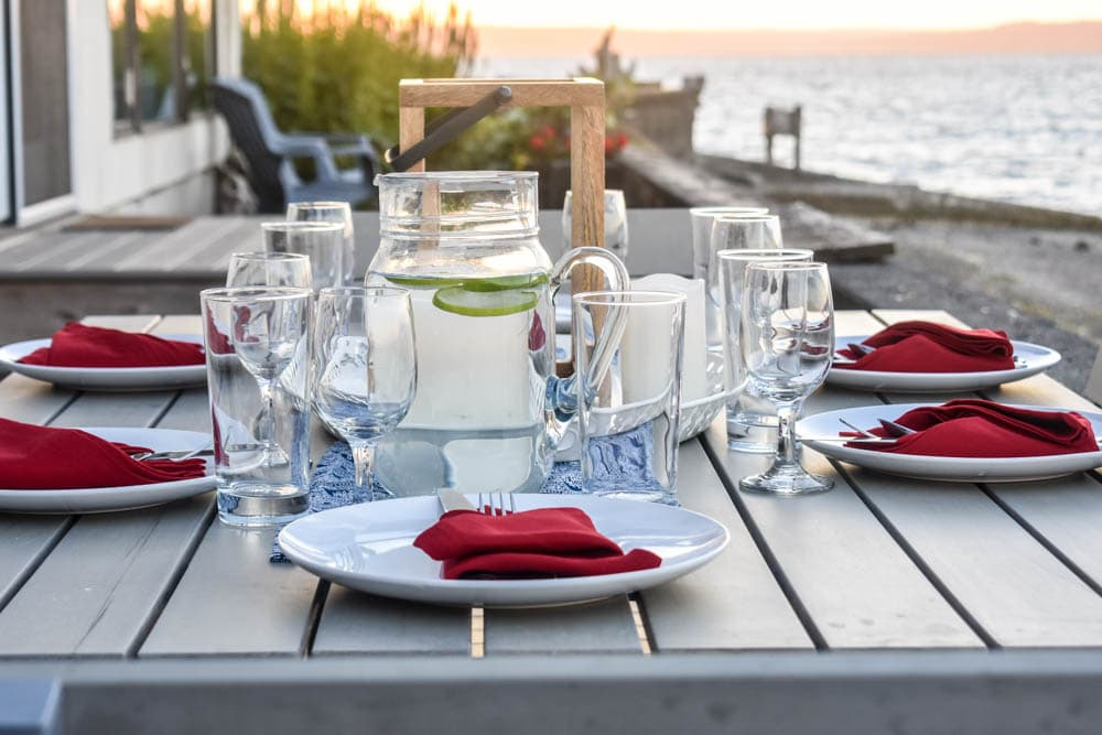 Table set for a 4th of July dinner with navy blue and white table runner and red cloth napkins, and sunset in background