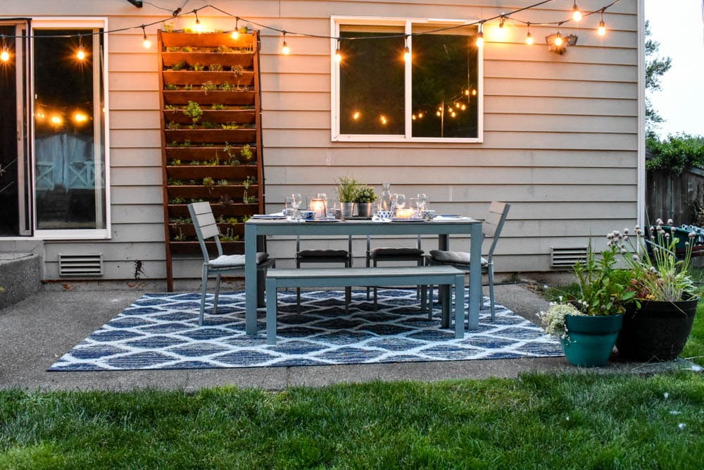 outdoor dining patio with string lights and candle lanterns