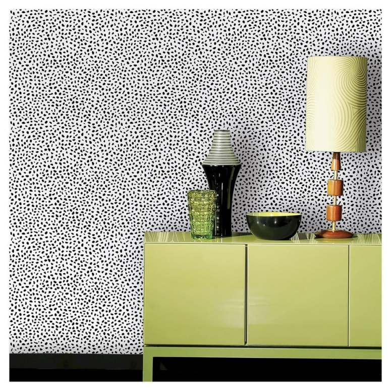 photo of white wallpaper with black speckles with green cammode and lamp
