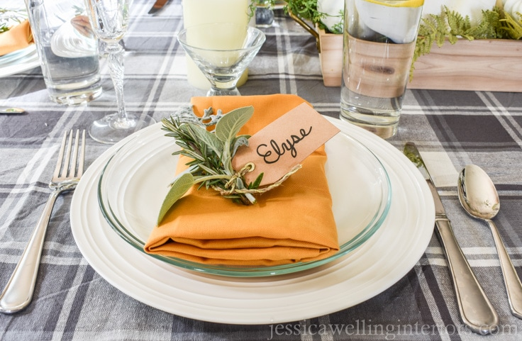 image of how to create a Thanksgiving table setting with mustard yellow napkin and fresh herbs