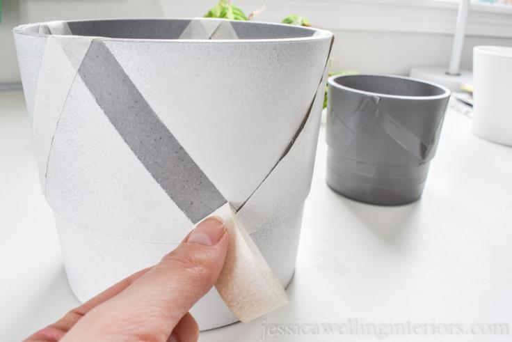 image of hand decorating modern indoor planter