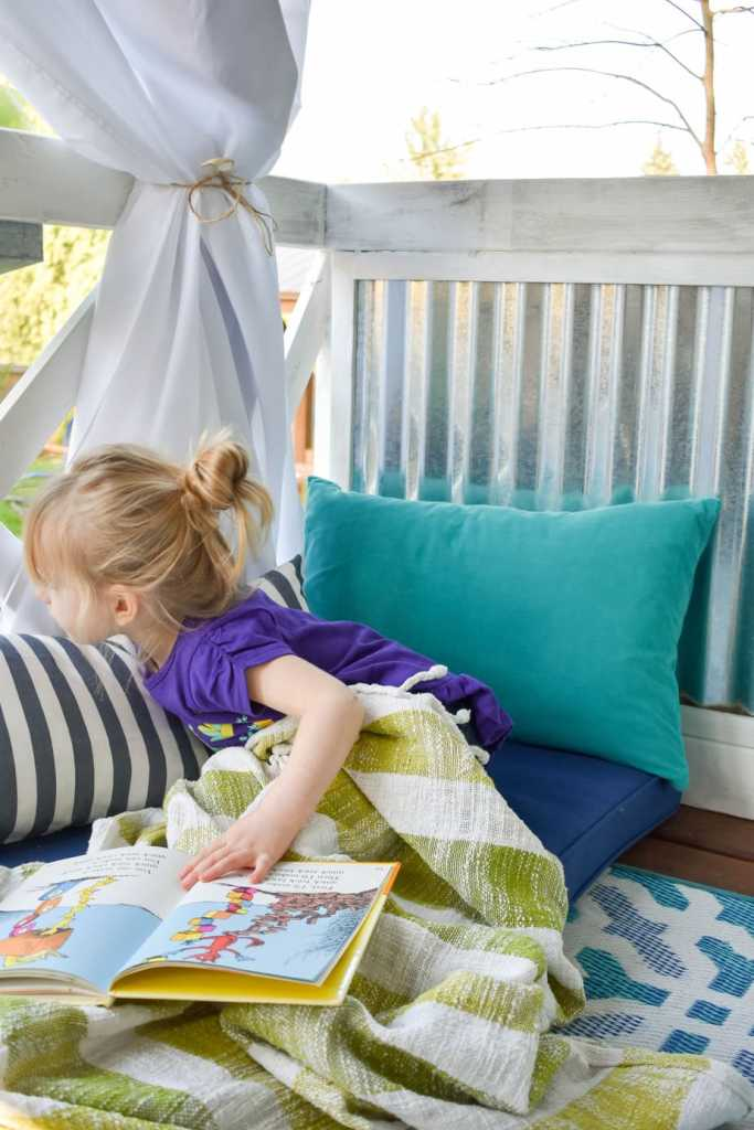 image of inside of playhouse with child reading in reading nook