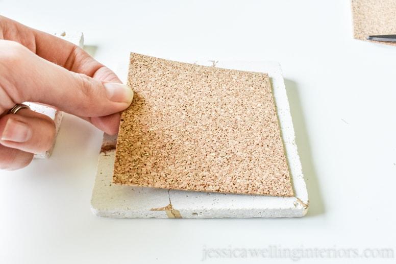 image of someone putting cork back on kintsugi tile coaster