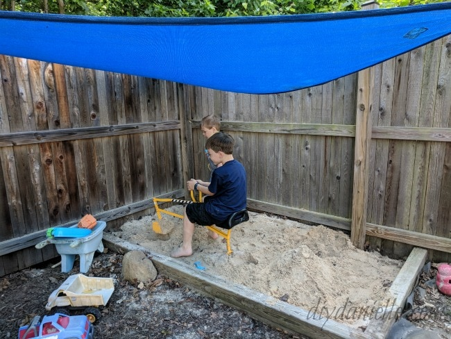 two small boys playing in sandbox covered in a blue shade sail