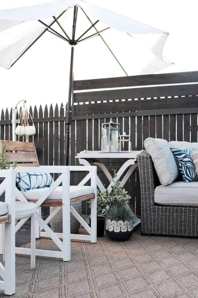 outdoor living room with white outdoor umbrella, outdoor sofa, and chairs