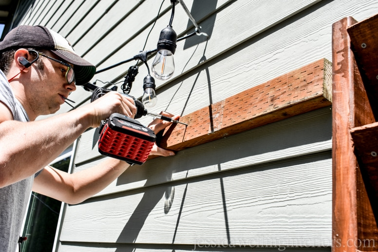 image of man attaching 2x4 mount to the side of house with screw gun