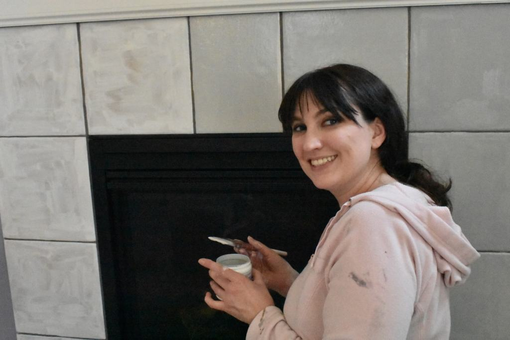 woman smiling in front of half-painted fireplace tiles