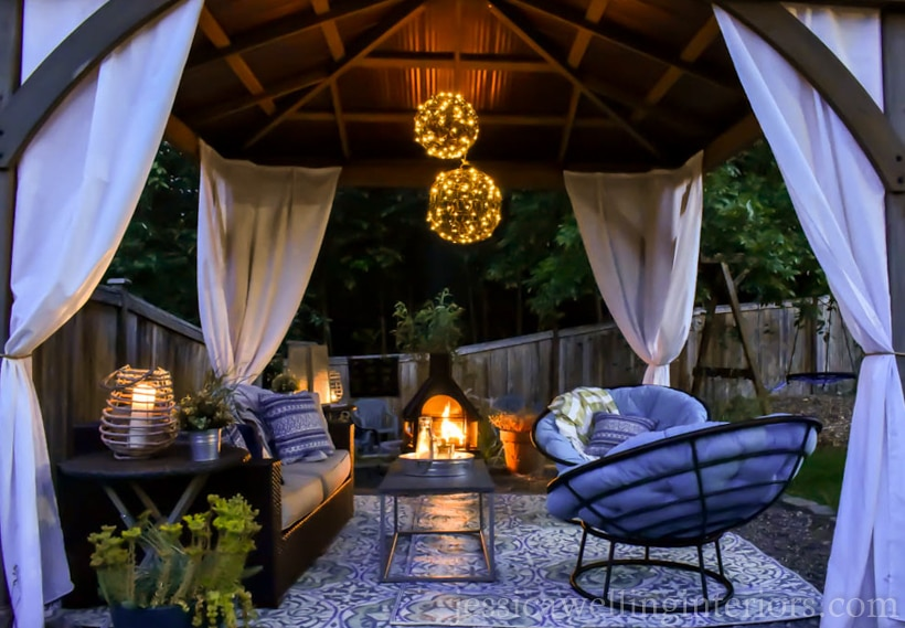outdoor living room in a gazebo with outdoor chandelier, outdoor fireplace, and candle lanterns