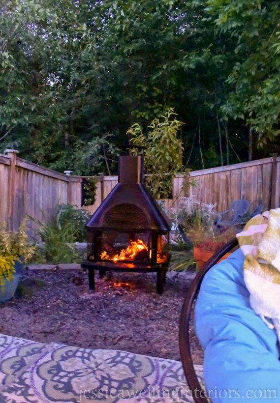 outdoor fireplace with papasan chair in the foreground