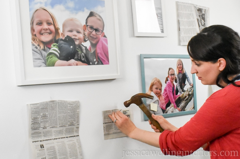 woman using a hammer to mount framed photos on gallery wall in beach house bunk room