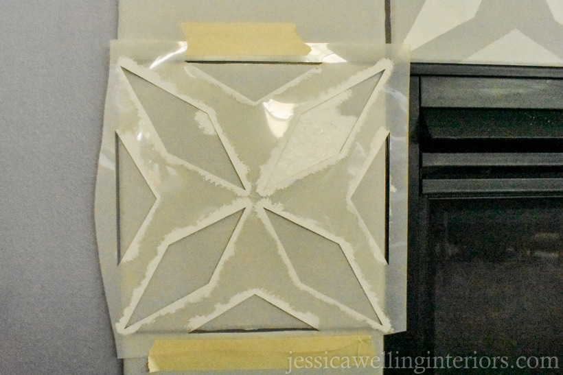 morroccan pattern tile stencil taped to fireplace tile with masking tape ready to be painted
