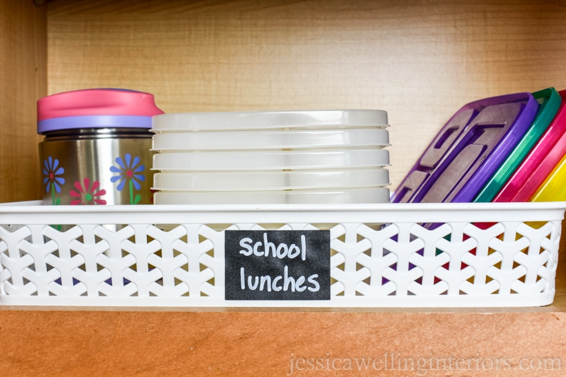 """kitchen cupboard with basket labeled """"school lunches"""" and thermos and stack of bento containers with lids"""