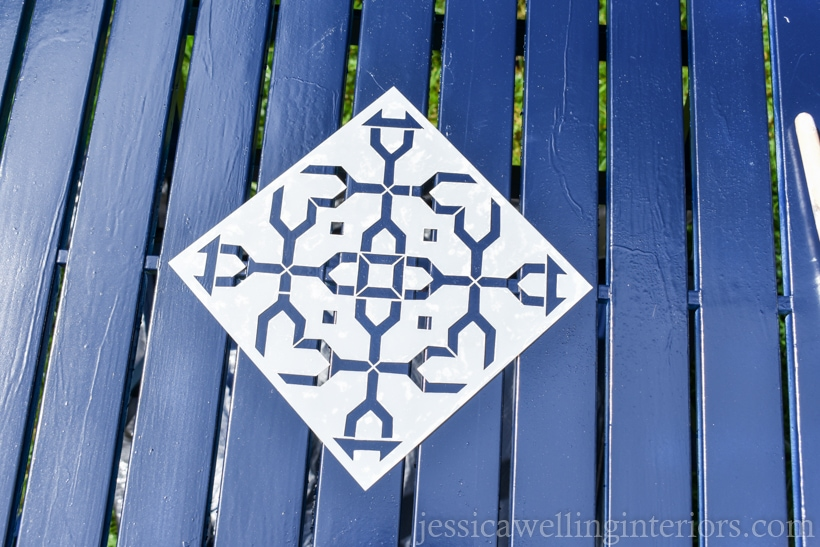 patio tabletop spray painted navy blue with stencil for fpainting furniture lined up in the center ready to be painted