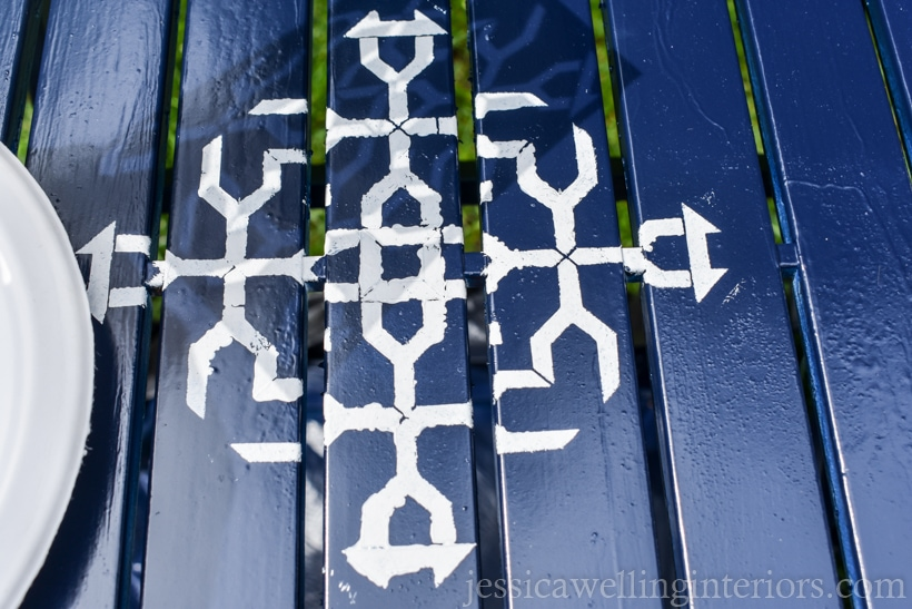 close-up of navy blue patio tabletop with single furniture stencil painted in white