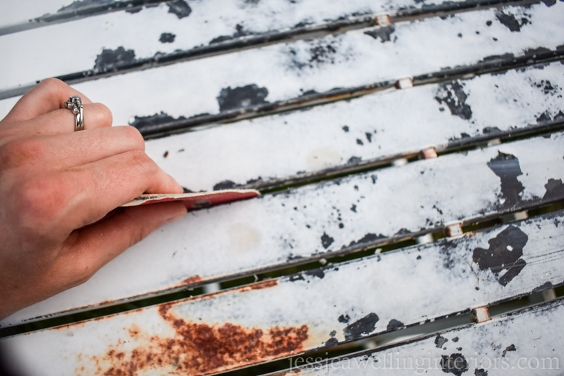 close-up of hand sanding peeling paint off of old rusty metal patio table
