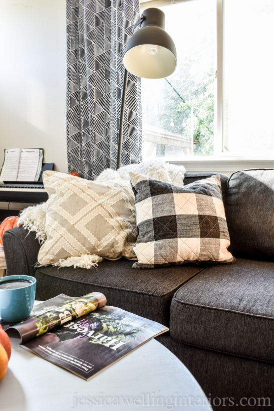 Neutral fall living room decor with charcoal sofa, fluffy white throw blanket, white pillow, and black and white buffalo plaid throw pillow