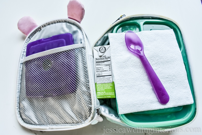 open childn's lunch box packed with an ice pack, a bento-style container, plastic spoon, and juice box
