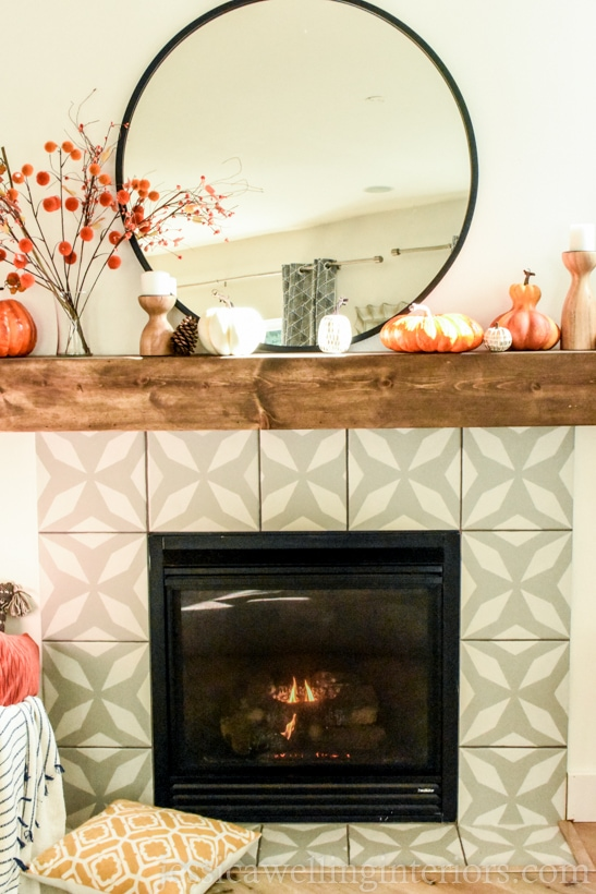 modern fireplace with round black-framed mirror, Fall decor stems in a vase, pumpkins, and a yellow throw pillow on the floor