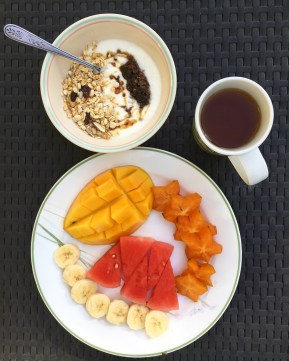 Local fruits, tea, and a yogurt bowl with honeycomb. Dream breakfast.