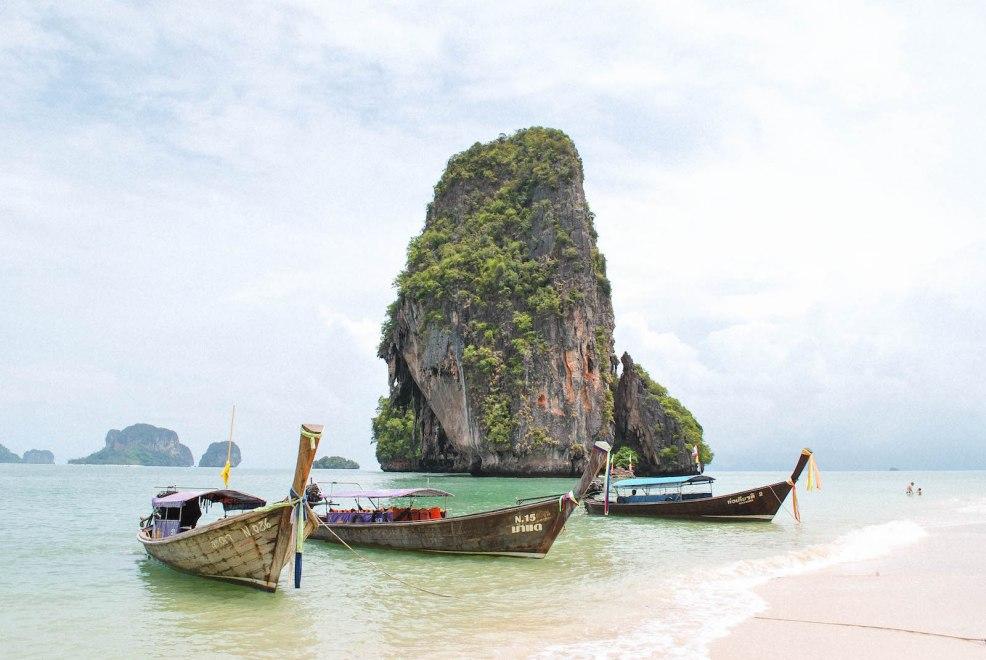 long tail boats and limestone cliffs at phra nang beach in Krabi thailand