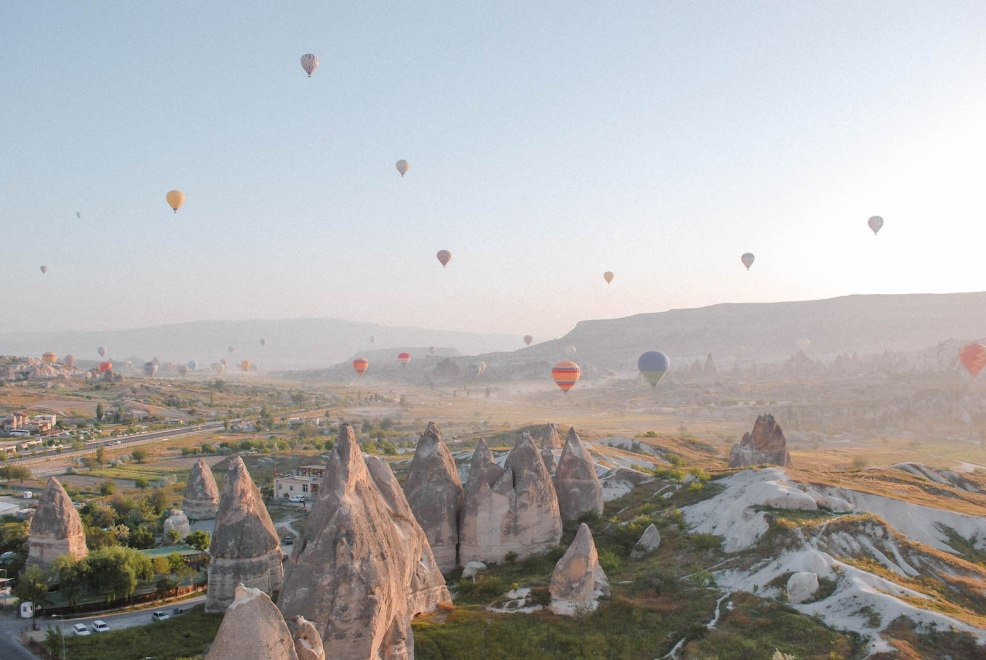 sunrise in Cappadocia with hot air balloons rising