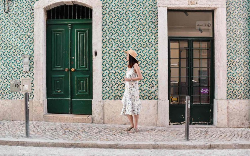 girl in front of green tiled wall and door in bairro alto Lisbon Portugal