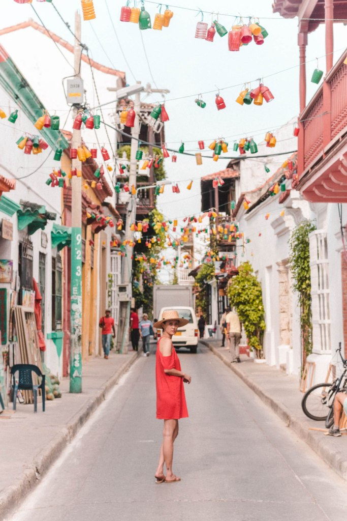 girl standing on colourful street in Cartagena