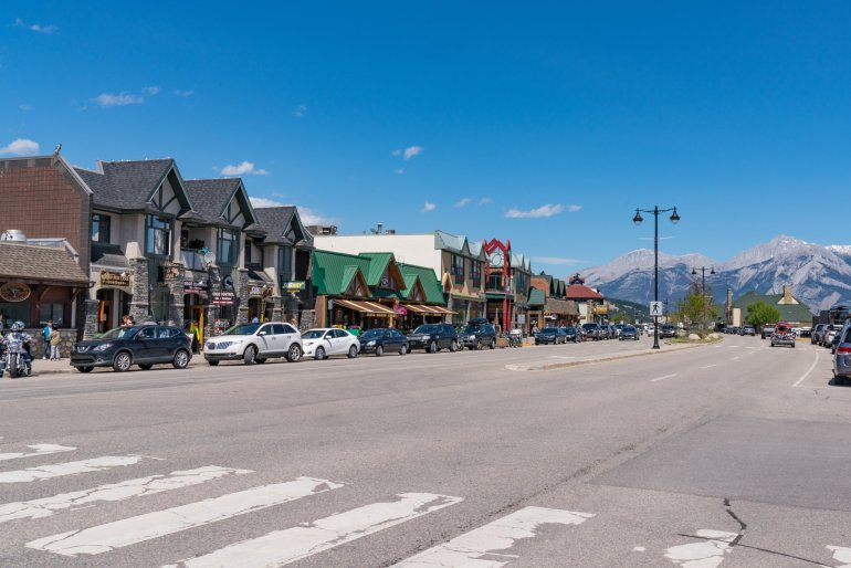 A view of the main street in downtown Jasper, with some rocky mountains in the background.