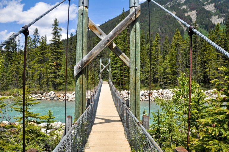 A view down a wooden suspension bridge that sits above a blue river.